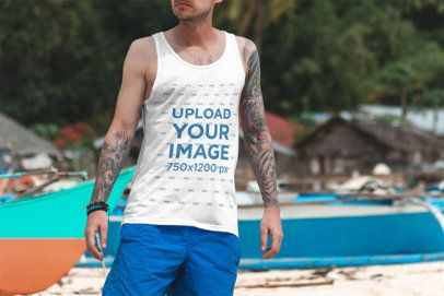 Tank Top Mockup of a Tattooed Man Standing by Some Boats at the Beach 3336-el1