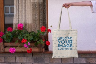 Mockup of a Tote Bag Against a Window with Flowers 3136-el1