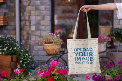 Mockup Featuring a Woman's Hand Holding a Tote Bag by Some Flower Pots 3137-el1