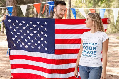 T-Shirt Mockup of a Blond Woman Standing Next to an American Flag 33031