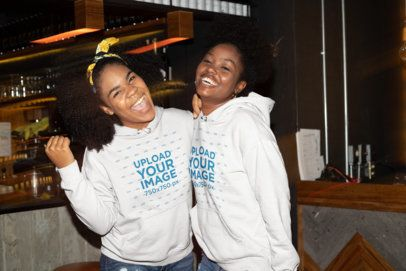 Mockup of Two Friends Wearing Hoodies at a Bar 32301