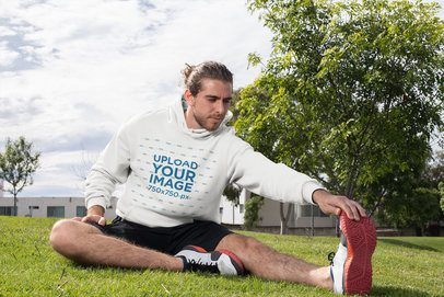 Hoodie Mockup of a Man Stretching His Leg on the Grass 32310