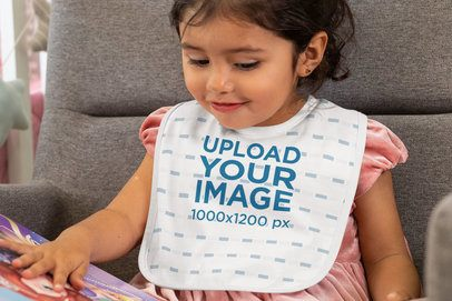 Baby Bib Mockup of a Girl Looking at a Picture Book 32516