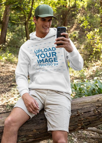 Pullover Hoodie Mockup Featuring a Man in the Woods Checking His Mobile 32222