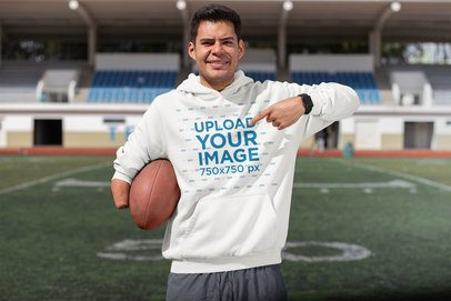 Mockup of a Happy Man Pointing at His Hoodie in a Football Stadium 32501