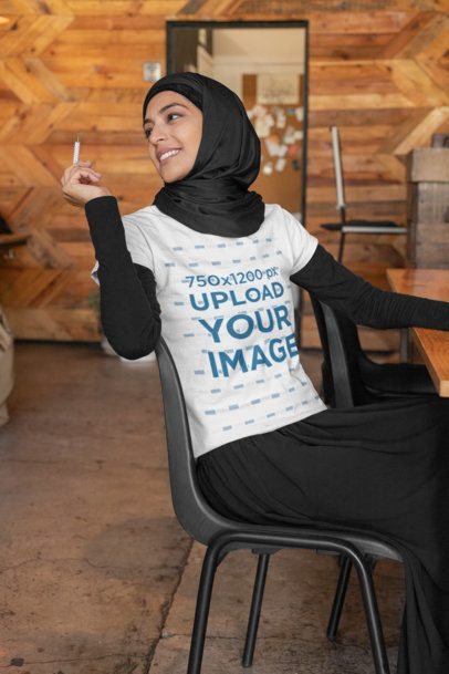 T-Shirt Mockup Featuring a Woman at a Coffee Store Holding a Pen 32396