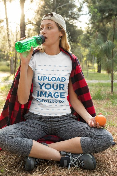 T-Shirt Mockup of a Woman at the Park Drinking Water 32244