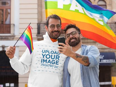 Pullover Hoodie Mockup Featuring a Couple Taking a Selfie in Front of an LGBT Pride Flag 32959