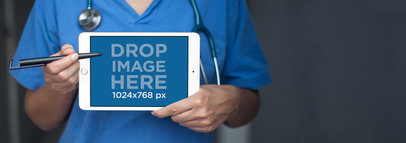iPad Mini in Landscape View Mockup of a Doctor Pointing to it a12412