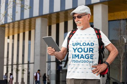 T-Shirt Mockup of a Happy Senior Man Using a Tablet in the Street 32884