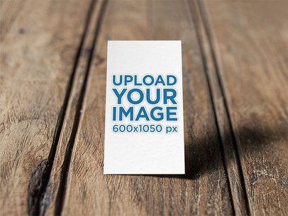 Mockup of an Embossed Vertical Business Card Standing on a Wooden Surface 33804