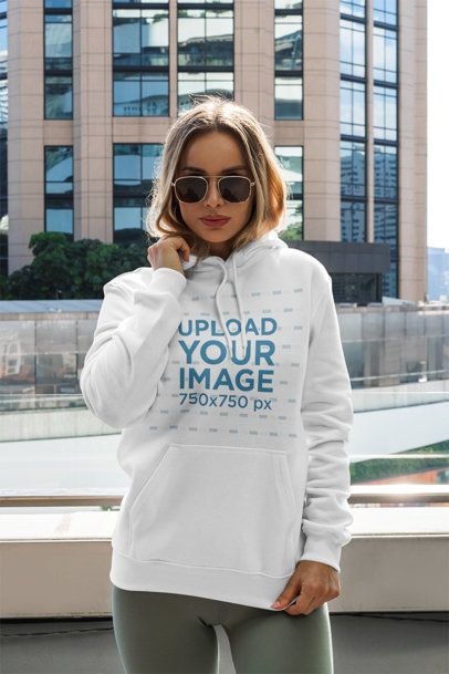 Mockup of a Woman with a Pullover Hoodie Posing by a Tall Building 3549-el1