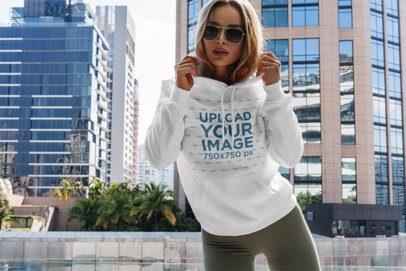 Hoodie Mockup Featuring a Woman Posing and Some Buildings in the Background 3550-el1