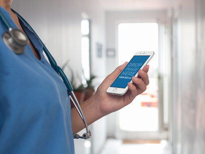 Mockup of a Female Doctor Using an iPhone in Portrait Mode in a Hospital 12411