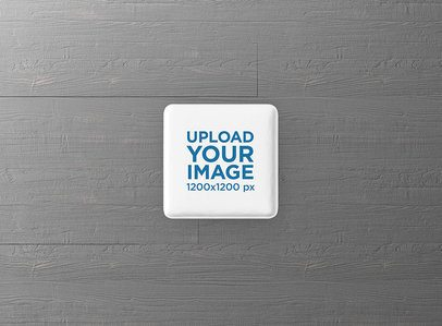 Square Pin Button Mockup Featuring a Grey Wooden Surface 3526-el1