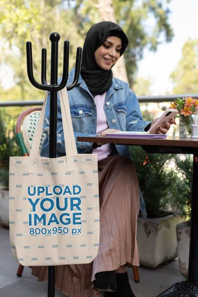 Tote Bag Mockup Featuring a Woman Wearing a Hijab and Using Her Phone at a Restaurant 32422