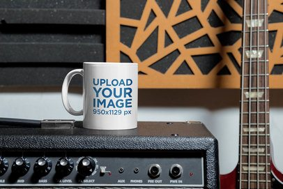 Mockup of an 11 oz Coffee Mug Placed Next to a Bass Guitar 33331