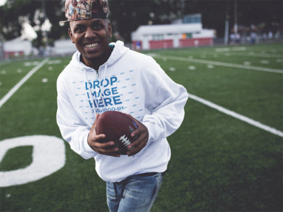 Smiling Young Black Man Playing Football Wearing a Hoodie Mockup b12450