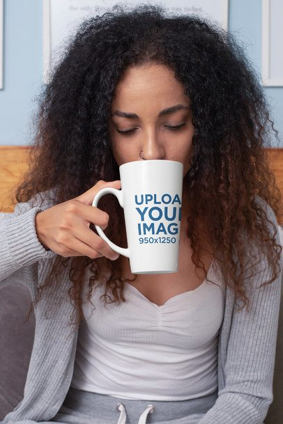 Mockup of a Woman Drinking From a 15 Oz Conical Coffee Mug While Sitting on a Bed 33186