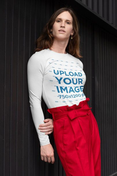 Mockup of a Woman Wearing a Customizable Long Sleeve Tee and Leaning Against a Dark Wall 32947