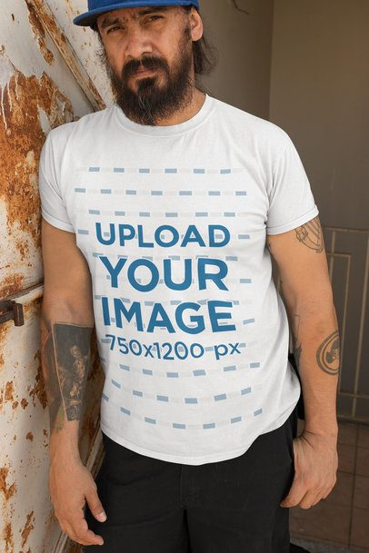 T-Shirt Mockup Featuring a Bearded Man Leaning Against a Rusty Wall 32841