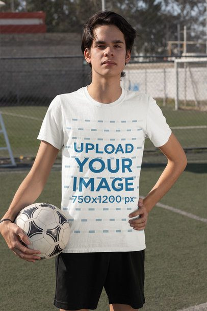 T-Shirt Mockup Featuring a Serious Teenage Boy Holding a Soccer Ball 33569