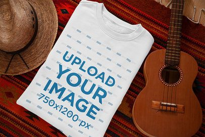 Mockup Featuring a Folded Crewneck Sweatshirt Placed Next to a Ukulele 33993