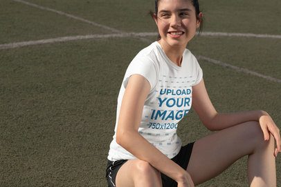T-Shirt Mockup of a Girl Sitting on a Soccer Field 33572