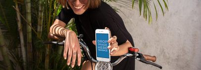 Mockup Featuring a Woman Smiling While Holding an iPhone in a Bike 12950wide