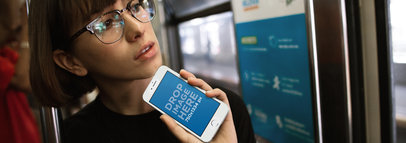 Mockup of a Woman Holding an iPhone Next to Her Face in The Subway 12961wide