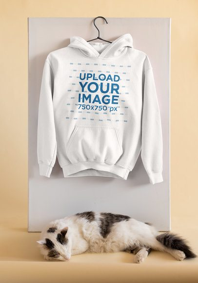 Mockup of a Pullover Hoodie Hanging by a Sleeping Cat 33755