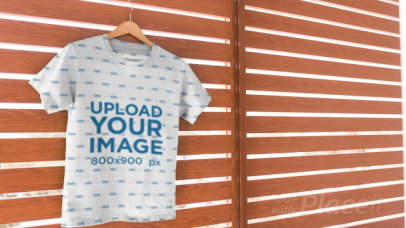 Video of a Sublimated T-Shirt Hanged on a Wooden Surface 13858