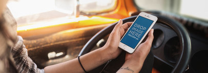 Mockup of a Woman Holding an iPhone in Portrait Position in the Driver's Seat 12933wide