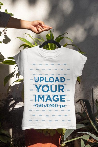 Mockup of a Woman's Hand Holding a T-Shirt by Some Garden Plants 33866