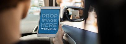 Mockup of a Man Holding an iPad in Portrait Position During a Car Ride 12962wide