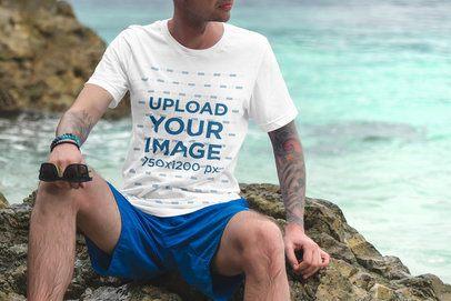 T-Shirt Mockup of a Tattooed Man Sitting on a Rock by the Sea 3327-el1