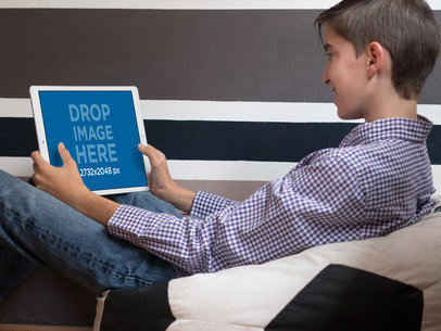 Young Boy Playing on his iPad Pro in Landscape Position Mockup at his House a13054wide