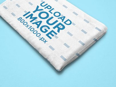 Mockup of a Folded Blanket Featuring a Customizable Background 25531