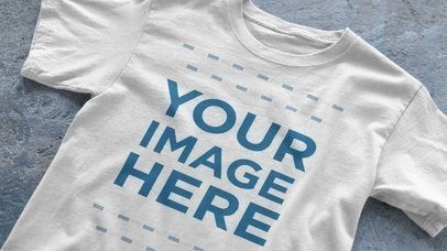 Single T-Shirt Spread Over a Concrete Surface Closeup Video Mockup a12348