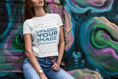 Mockup of a Woman in a T-Shirt Leaning on a Wall with Graffiti 4298-el1