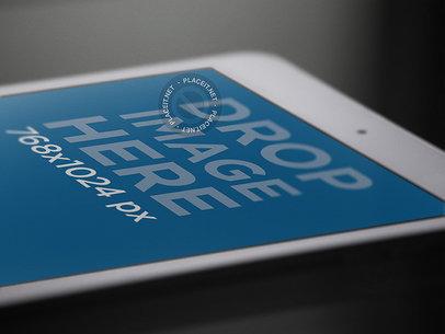 White iPad Mini Mockup in Angled Closeup View Over a Black Surface a12761
