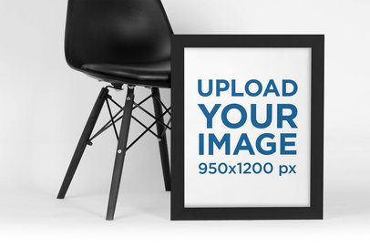 Mockup of a Framed Art Print Leaning Against a Dark Modern Chair 4474-el1