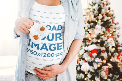 Mockup of a Pregnant Woman in a T-Shirt by a Christmas Tree 37253-r-el2