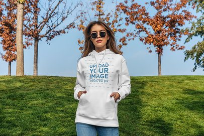 Pullover Hoodie Mockup of a Serious Woman Standing in Front of a Green Grass Hill 4774-el1