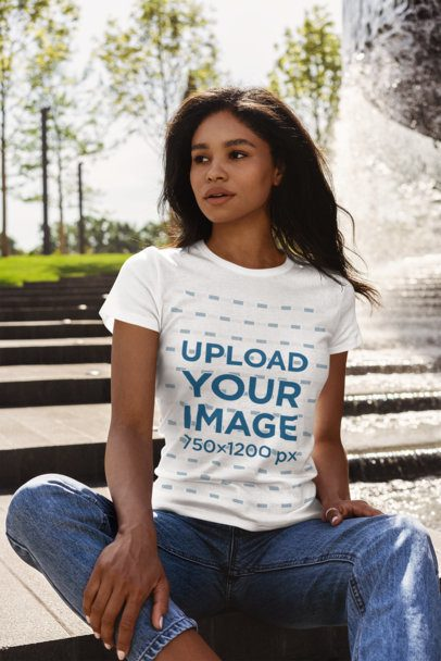 Mockup of a Woman Wearing a T-Shirt and Sitting by a Fountain 4814-el1