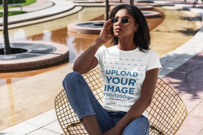 T-Shirt Mockup Featuring a Young Woman Sitting by a Large Fountain 4820-el1