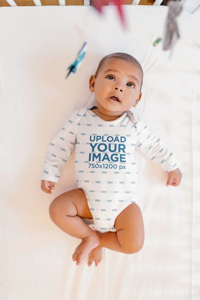 Sublimated Long Sleeve Onesie Mockup Featuring a Baby Lying on a Crib 35725-r-el2