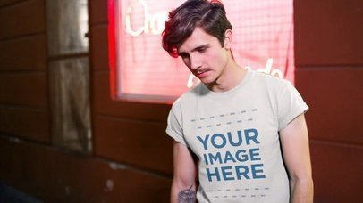 Hipster Man Wearing a Round Neck Tee Outside a Store at Night Mockup Video a13465
