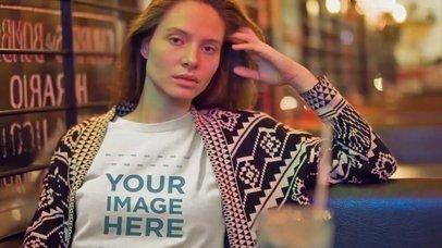 Mockup Video of a Young White Woman Wearing a T-Shirt at a Coffee Shop at Night a13405