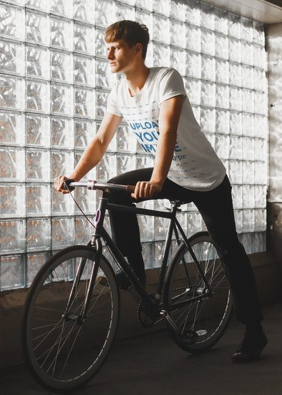 T-Shirt Mockup of a Young Man Riding a Bike Next to a Glass Wall 37798-r-el2